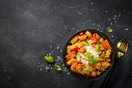 Pasta chicken with vegetables. Served with parmesan. Top view at black table.