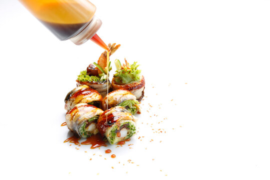 Topping, decorating unagi ebi ten roll set, with dressing. 6 piece sushi set with eel, shrimp in tempura, cucumber, dressing, on a white background, with a copy-space, a textspace. A packshot photo.