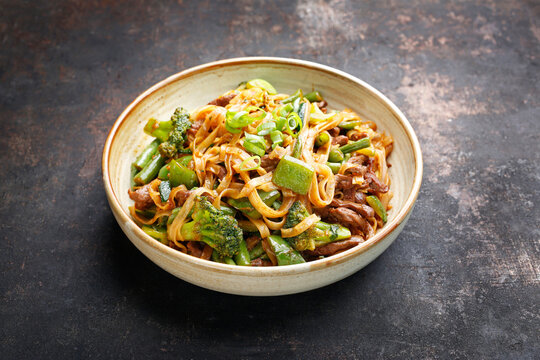Oriental noodles. Thai cousine dish. Beef fried on a wok with rice noodles, green beans, zucchini, pak choi and green peppers in spicy soy-oyster sauce, in a bowl, on black stony background.
