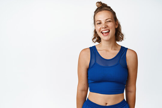 Portrait of happy sports woman winking, smiling and looking at camera, wearing blue activewear for fitness workout, white background