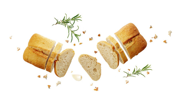 Cutting  fersh baked ciabatta loaf with  crumbs and rosemary herb twig flying isolated on white