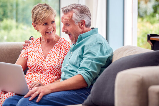 Senior Retired Couple Sitting On Sofa At Home Shopping Or Booking Holiday On Laptop