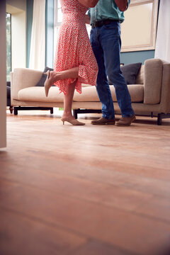 Close Up On Legs As Romantic Senior Retired Couple Dancing In Lounge At Home Together