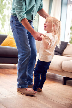 Granddaughter Dancing On Grandfathers Feet In Lounge At Home