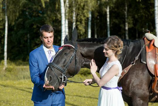 Happy wedding couple with dark horse