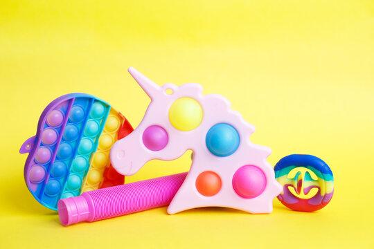 colorful antistress sensory fidget toys on a yellow background.