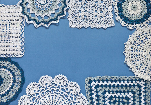 Top view of handmade lace doilies on a blue background in the form of a frame for text or ad. Winter handicrafts and hobbies. Xmas presents. DIY concept. Flat lay, close up, copy space, mock up