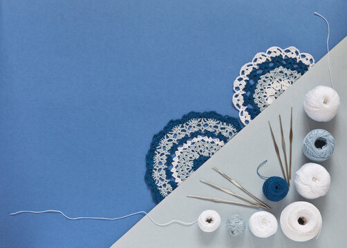 Top view of beautiful lace doilies crocheted from white, gray and blue cotton yarn. Balls of yarn for hand crochet and a set of hooks nearby. Flat lay, close-up, copy space, mock up, place for text