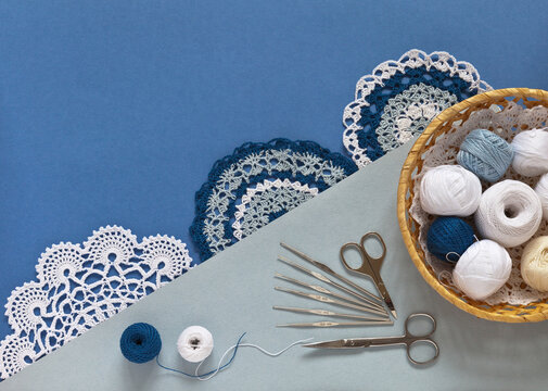 Beautiful crochet lace doilies. Balls of cotton yarn for hand crochet in wicker basket and set of hooks of different sizes on blue and gray background. Flat lay, copy space, close-up, top view, mockup