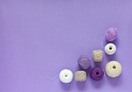 Various types of white, beige in purple natural cotton yarn for hand crocheting on a violet background. DIY concept. Needlework and knitting as a hobby and pleasure. Empty space for text, flat lay