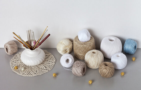 Various types of white and beige natural cotton yarn for hand crocheting and a set of crochet hooks in a vase on the table. DIY concept. Needlework and knitting as a hobby and pleasure