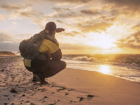 Man Tourist Thinking And Meditates On Beach At Sunrise. Relaxation And Harmony. Man Shadowing Eyes