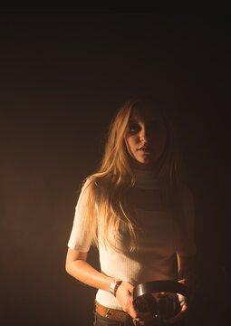 Portrait of caucasian female music artist holding headphones against grey background