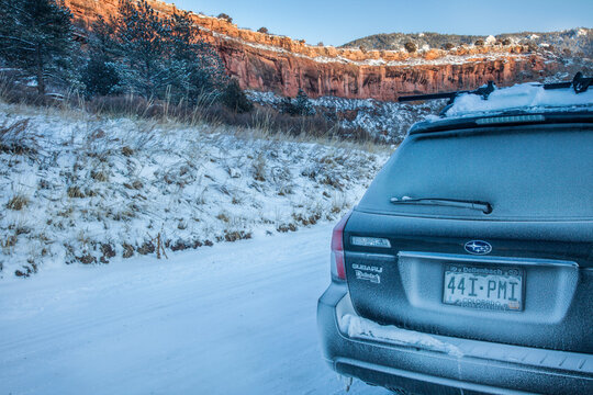 Fort Collins, CO, USA - December 24, 2009: Winter driving in Colorado, Subaru Outback car on a backcountry road covered by snow and frost.