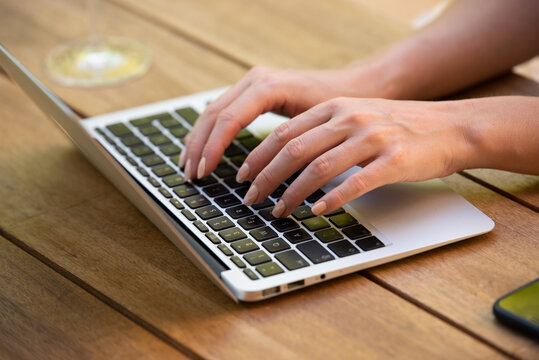 Close-up of woman's hand while typing on laptop