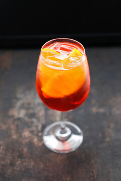 A top view of a red cocktail, colourful lemonade, red drink in a glass, with ice cubes and orange wedges, on a black stony background, on a bar.