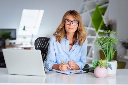 Businesswoman using a laptop while sitting at office desk and working