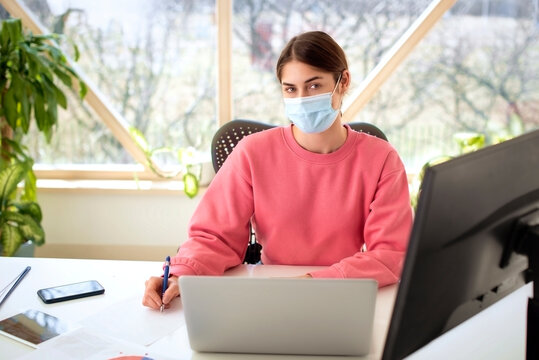 Young businesswoman wearing face mask while working on notebook at office desk