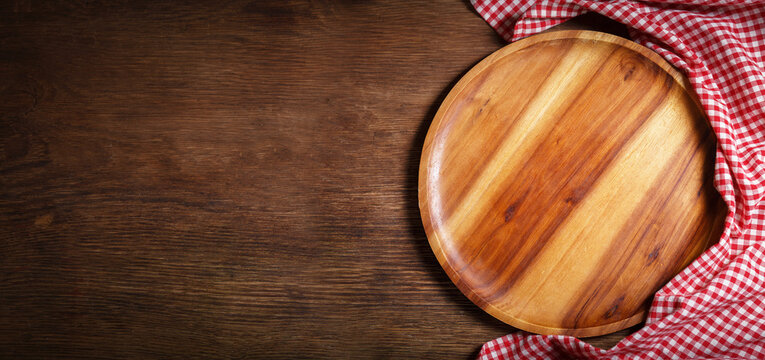 empty wooden plate with red tablecloth on a wooden background