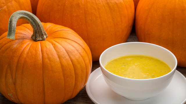 pumpkin cream soup - a bowl surrounded by pumpkins on a wooden table