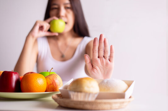 Asian woman hands stop to bread and holding green apple on white background,Healthy diet,Dieting concept