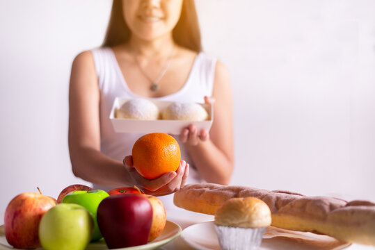 Asian woman hands holding orange and bread on white background,Healthy diet,Dieting concept