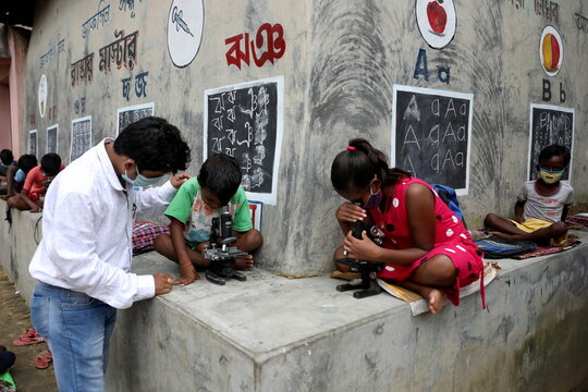 Deep Narayan Nayak teaches children how to use microscope in an open-air class outside the houses with the walls converted into black boards at Joba Attpara village