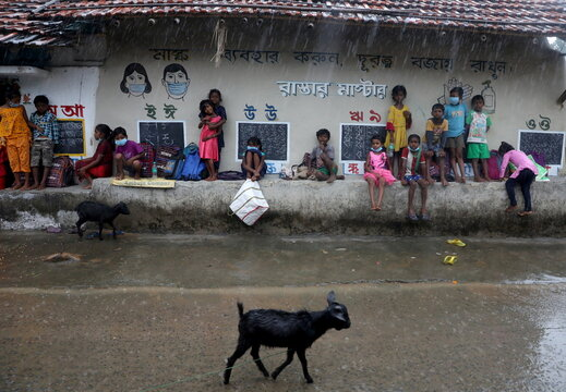 Children wait for rain to stop as they attend open-air classes outside the houses with the walls converted into black boards at Joba Attpara village