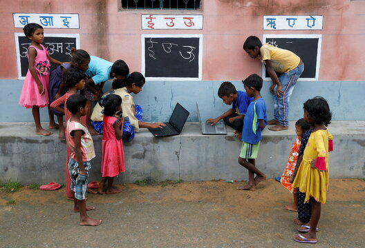 Children use laptops in an open-air class outside a house with the walls converted into black boards at Joba Attpara village