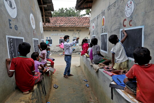 Deep Narayan Nayak teaches children in an open air class outside the houses with the walls converted into black boards at Joba Attpara village