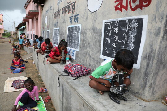 Children use microscopes as they attend an open-air class outside houses with the walls converted into black boards at Joba Attpara village