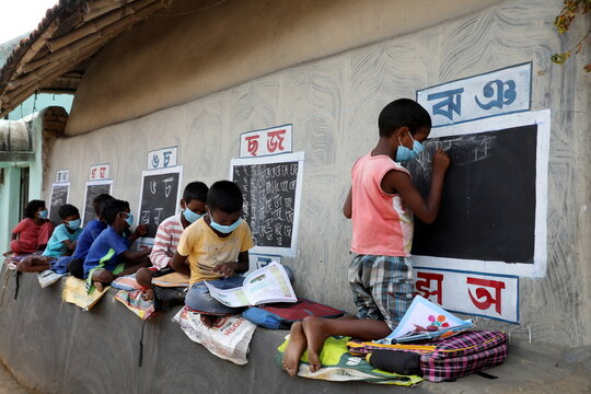 Children attend an open-air class outside the houses with the walls converted into black boards at Joba Attpara village