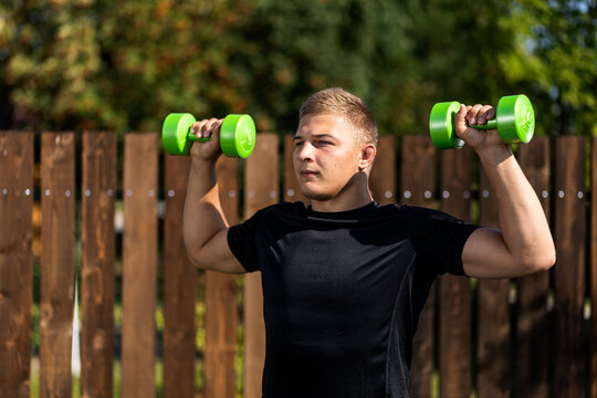 A cheerful athlete with blonde hair does exercises to strengthen the biceps with dumbells in  garden. The young man goes in for sports in park.