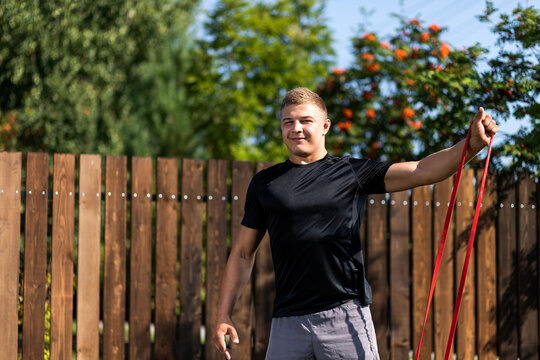 Close up of the young man goes in for sports at home in  backyard in summer day. Young sportsman doing  exercise  with sport rubber