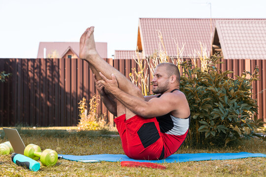 Close-up of a young man in a sports uniform try meditates in  difficult position, stretching on the floor  in backyard  in summer say