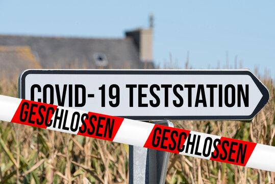 Schild auf Covid-19 Teststation und Absperrband Geschlossen