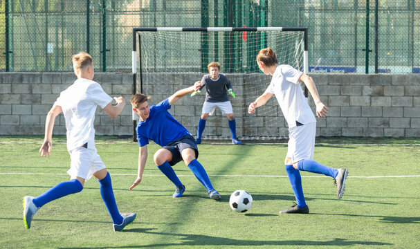 Game moments of football match between two teams of teenagers in white and blue shirts