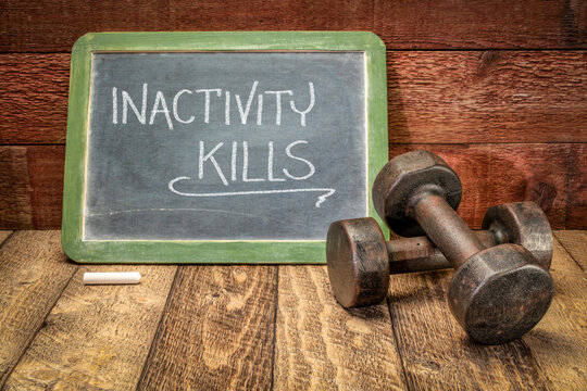 inactivity kills motivational concept, white chalk writing on a slate blackboard with a pair of vintage dumbbells, sedentary lifestyle, fitness and personal development