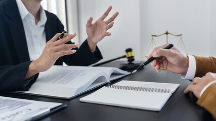 law,libra scale and hammer on the table, 2 lawyers are discussing about legal provision, law...