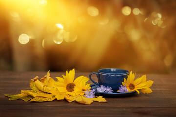 Fototapeta filiżanka kawy w jesienny poranek, kawa o poranku, żółte kwiaty słonecznika obraz