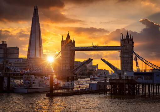 Beautiful sunset view to the Tower Bridge of London, United Kingdom, lifted up so ships can pass by on the Thames River