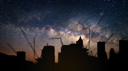 Silhouette of crane tower in the construction site city building with stary night sky and milky way background