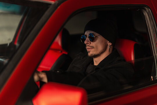 Young handsome hipster man with fashion sunglasses in a hat and coat sits and rides in the car. Traveling by transport
