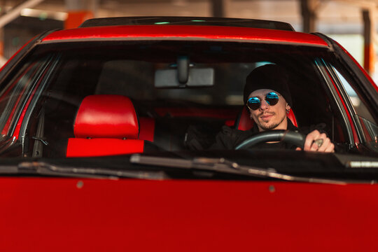 hipster man in sunglasses sits behind the wheel of a red old car. Travel by auto