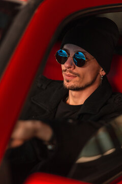 stylish handsome man with sunglasses in hat and coat sits behind the wheel of a red old car