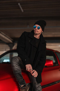 Elegant casual handsome man in stylish blue sunglasses in a black fashionable coat with a hat sits on a red car on the street