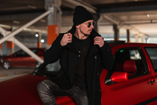 Handsome guy model with sunglasses in fashionable black clothes with a coat and a hat near a red car in the city