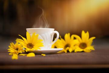 Fototapeta filiżanka kawy w jesienny poranek, kawa o poranku i żółte kwiaty słonecznika obraz