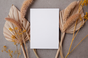 Bohemian blank invitation card surrounded by natural dried palm leaf and grasses. Wedding and...