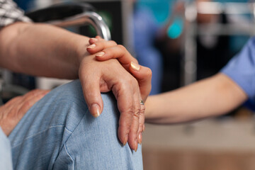 Social assistant worker consoling handicapped pensioner patient touching hands during homecare service. Healthcare support assistance. Social services nursing at home. Caregiver nurse